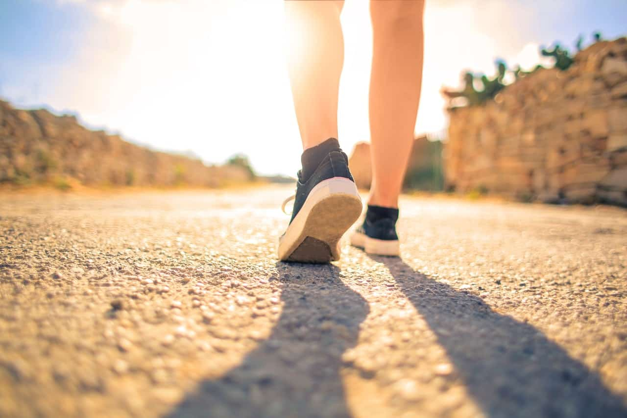 woman-walking-on-pathway-under-the-sun-3779751